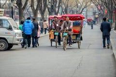 PEKING, CHINA - 12. MÄRZ 2016: Touristen in einer Rikscha in einer Hütte Stockfotografie