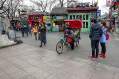 PEKING, CHINA - 12. MÄRZ 2016: Touristen in einer Rikscha in einer Hütte Stockfotos