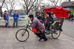 PEKING, CHINA - 12. MÄRZ 2016: Touristen in einer Rikscha in einer Hütte Lizenzfreie Stockfotos