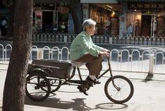 PEKING, CHINA - 12. MAI 2013: Alte Frau auf Fahrrad Stockfotografie