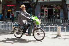 PEKING, CHINA - 12. MAI 2013: Alter Mann auf elektrischem Motorrad Lizenzfreies Stockfoto