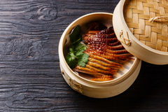 Peking Duck. In bamboo steamer with fresh cilantro on black burned wooden background Stock Images