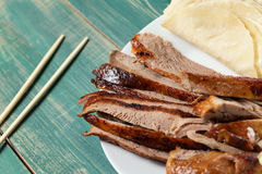 Peking Duck - Chinese roast duck pancakes on wooden green table with chopsticks close up royalty free stock photos