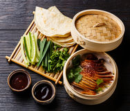Peking Duck with cucumber, onions, cilantro and pancakes. Peking Duck in bamboo steamer served with fresh cucumber, green onions, cilantro and roasted wheaten royalty free stock image