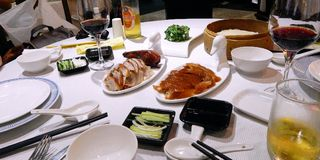 Peking duck is served at the table of the restaurant `Peking duck` in Shanghai, China. Table with white tablecloth, white dishes and served with chopped duck in Royalty Free Stock Images