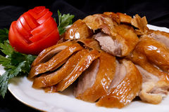 Peking duck. Sliced, served with tomato and parsley Royalty Free Stock Image
