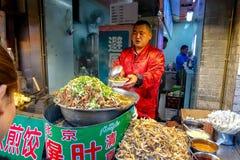 PEKING KINA - MARS 11, 2016: Matförsäljare erbjuder dess produkt Royaltyfri Bild