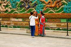 Peking Kina, 06/06/2018 två kinesiska flickor i nationella dräkter fotograferas nära väggen av nio drakar i förbjuden royaltyfri foto