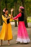 Peking Kina 07 06 2018 två lyckliga kvinnor i ljusa klänningar dansar i parkerar arkivfoto