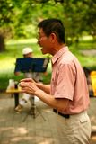 Beijing, China - June 7, 2018: A Chinese retiree performs an aria from a Peking opera in a public park. stock photo
