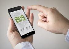 Pekskärmsmartphone med online-marknadsföring på skärmen Arkivbild