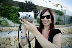 Película de la mujer y usar una cámara de vídeo Imagen de archivo libre de regalías