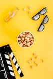 Película de observação Clapperboard, vidros e pipoca na opinião superior do fundo amarelo Imagem de Stock