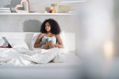Película de observación de consumición del café de la mujer en cama el domingo Imagen de archivo libre de regalías