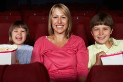Película de observación de la madre en cine con dos niños fotos de archivo libres de regalías