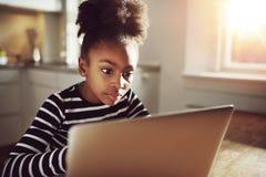Película de observación de la muchacha adolescente negra en el ordenador portátil seriamente Imagenes de archivo