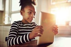 Película de observación de la muchacha bastante negra en su tableta Imagen de archivo libre de regalías