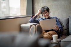 Película de observación del hombre asiático joven del ordenador portátil Imagen de archivo libre de regalías