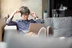 Película de observación del hombre asiático joven del ordenador portátil Foto de archivo libre de regalías