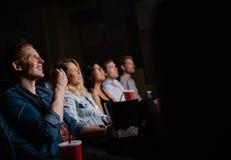 Película de observación del hombre joven con los amigos en cine imágenes de archivo libres de regalías