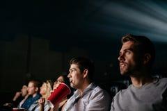 Película de observación del hombre joven con los amigos en pasillo del cine imagen de archivo libre de regalías