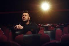 Película de observación del hombre pensativo joven en teatro Imágenes de archivo libres de regalías