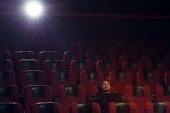Película de observación del hombre pensativo joven en teatro Foto de archivo