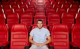 Película de observación feliz del hombre joven en teatro Fotos de archivo libres de regalías