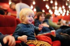 Película de observación de la historieta del niño pequeño lindo en el cine fotos de archivo libres de regalías