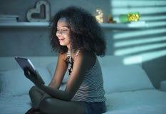 Película de observación de la muchacha hispánica con la tableta y la risa Foto de archivo