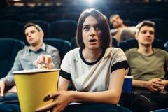 Película de observación sorprendida de la mujer en cine Fotografía de archivo