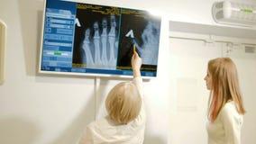 Película de radiografía femenina profesional de la lectura del doctor del cerebro y en el teléfono 4k almacen de video