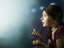 Película de terror de observación de la muchacha adolescente con palomitas de maíz Foto de archivo