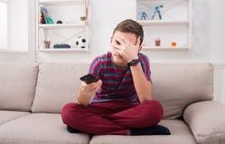 Película de terror de observación del muchacho en el sofá en casa Fotografía de archivo libre de regalías
