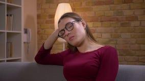 Pel?cula femenina morena joven y hermosa del retrato del primer de los relojes en la TV que es agotada y atenta en casa almacen de metraje de vídeo