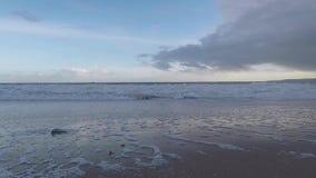 Película lenta, playa arenosa hermosa y onda inundando la playa, cielo azul y nubes metrajes