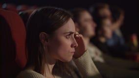 Película que emociona de observación concentrada de la muchacha en el cine Disfrute del concepto del cine almacen de video