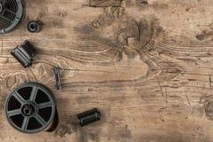 película y envase de la foto de 35 milímetros para el desarrollo de la película que miente en piso de madera Foto de archivo