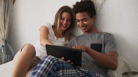 Películas de observación de risa de los pares multiétnicos jovenes en cama en la tableta digital Tiro a cámara lenta metrajes