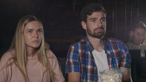 Películas del reloj de la gente joven cuidadosamente en cine Imagen de archivo