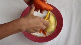 Peladura apagado de las zanahorias en la placa almacen de video