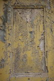 Peladura de la pintura amarilla de la mostaza en una puerta Imagen de archivo