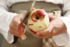 Peladura de una manzana con un cuchillo grande Fotografía de archivo