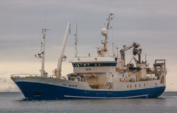 Pelagic fishing Vessel. Erika GR-18-119 from Tasiilaq Greenland approaching port in Helguvik, Iceland, fully loaded with Capelin Stock Photos