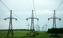 Pelare av linjen maktelektricitet på grönt fält Fotografering för Bildbyråer