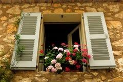 Pelargonien im Fenster im mittelalterlichen Dorf von Gourdon, Provence, Frankreich Stockbilder
