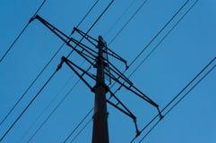 Pelarhög-spänning kraftledningar mot den blåa himlen för afton arkivfoton