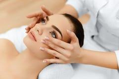 Pele, cuidado do corpo Mulher que obtém a massagem de cara dos termas da beleza Treatmen