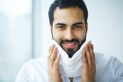 Pele da cara da limpeza do homem com toalha branca Imagem de Stock