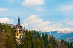 Peles castle clock tower, Sinaia, Romania. Blue sky, white cloud. S and mountains in the background stock image
